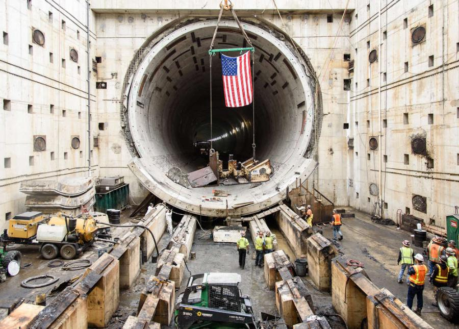 In tribute to Seattle's tunneling machine Bertha, the American flag flies above the last piece of the machine as it is lifted out of the disassembly pit near Seattle Center.